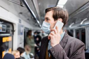 Mężczyzna w maseczce rozmawia przez telefon w pociągu